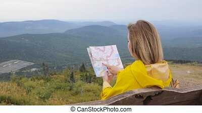 Young female hiking im yellow raincoat with a backpack in mountains holding paper map in hands.
