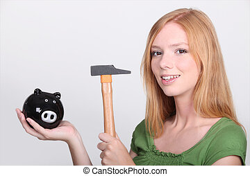 Young female holding piggy bank and hammer