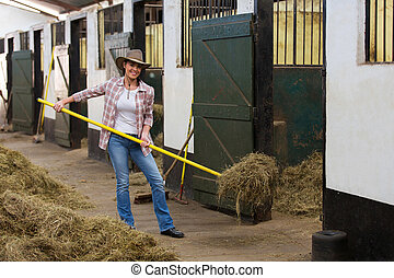 female horse breeder working inside stable - young female ...