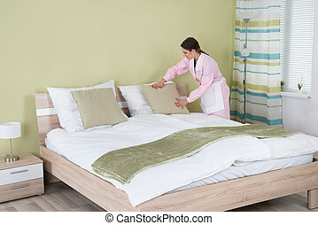 Young Female Housekeeper Arranging Pillow On Bed In Room