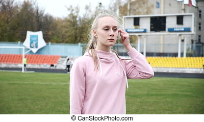 young female in sportswear standing on background of green football field lawn