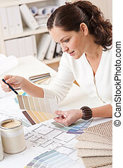 Young female interior designer working at office with color...
