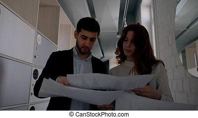 Young female intern with red hair showing financial graphs to her male boss