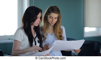 Young female is asking boss for approval of documents. Woman...