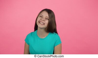 Young female is laughing in the studio on pink background....