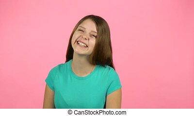 Young female is laughing in the studio on pink background -...
