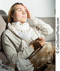 Young female is watching TV and sitting on sofa