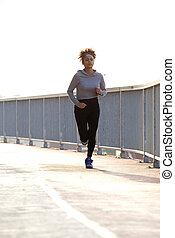 Young female jogger running outdoors
