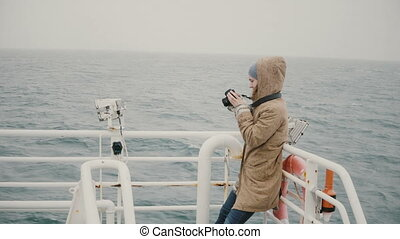 Young female journalist standing on the board of the boat...