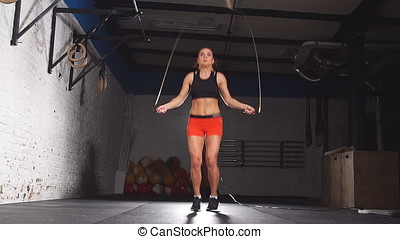 Young female jumping on the skipping rope in a gym. Slow motion.