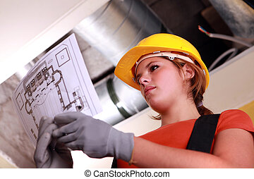Young female laborer reading plan