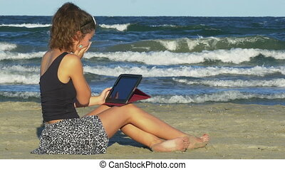 Young female laughing hard while having funny chat session on her tablet pc on the beach