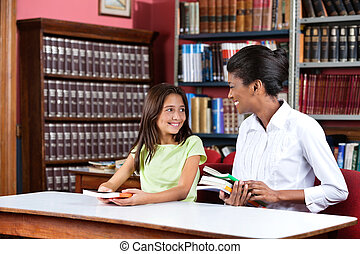 Young female librarian looking at schoolgirl while sitting with books at table in library
