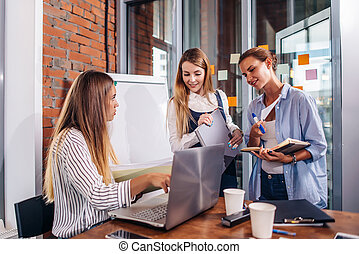 Young female manager sitting at desk pointing at laptop explaining giving tasks to her employees standing writing the information in notebooks in office.