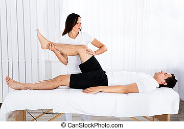 Young Female Masseur Giving Leg Massage To Relaxed Man In Spa