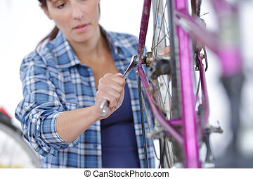 young female mechanic in bicycle store