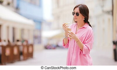 Young female model eating ice cream cone outdoors. Summer concept - woamn with sweet ice-cream at hot day