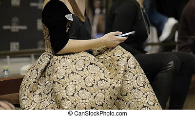 Young female model in a beautiful dress couture uses the phone on the backstage of fashion week