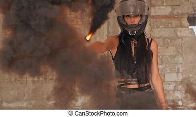 slow motion medium shot woman biker posing looking camera waving black smoke grenade