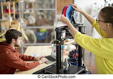 Young female office worker changing spool with red filament on 3d printer