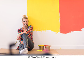 young female painter sitting on floor