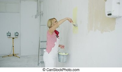 Young female painting wall with brush - Side view of...
