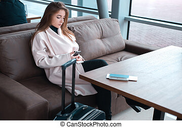 Young female passenger using phone at the airport.