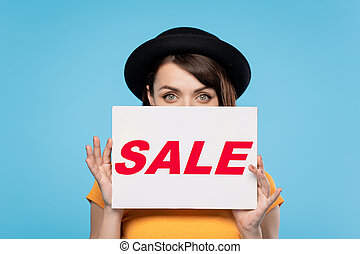 Young female peeking out of paper poster with seasonal sale announcement