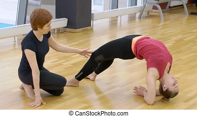 Young female performs asana with trainer in fitness center....