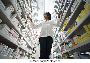 Young Female Pharmacist Arranging Stock In Shelves At Pharmacy