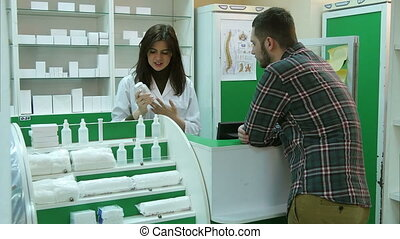 Young female pharmacist hrlping male client to buy tablet at pharmacy