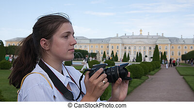 Young female photographer at park against sky