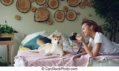 Young female photographer is shooting beautiful pet dog...