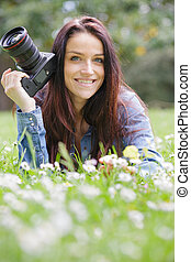 young female photographer shooting in a green natural setting