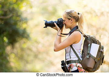 female photographer taking photos in mountain valley - young...