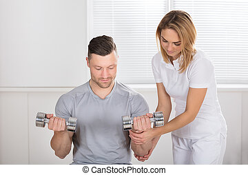 Young Female Physiotherapist Helping Man To Exercise