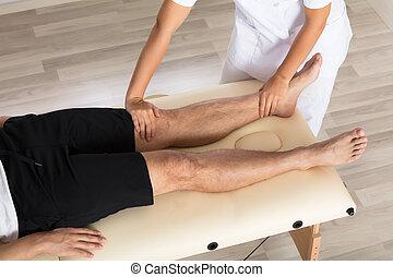 Physiotherapist Massaging Man's Leg