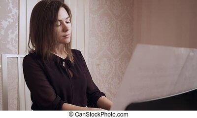 Young Female Pianist Playing Grand Piano indoors