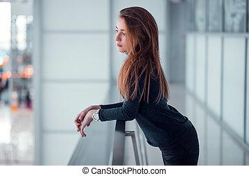 Young female  posing on glazed balcony.