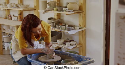 Young female potter working in her studio - Front view of a ...
