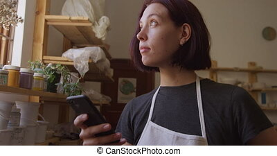 Young female potter working in her studio