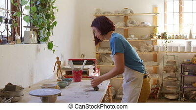 Young female potter working in her studio - Side view of a ...