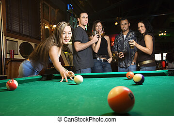 Young female preparing to hit pool ball. - Young asian woman...