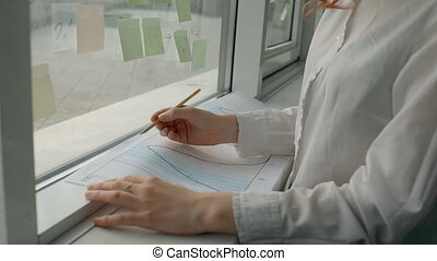 Young female professional writing on documents standing by window in modern office.