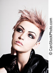 An attractive young female with a serious expression is wearing a punk hairstyle with pink hair. Vertical shot.