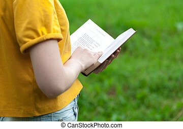 Young female reading book in summer park
