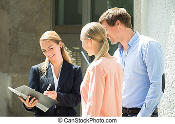 Real Estate Agent Explaining Contract To Couple - Young...