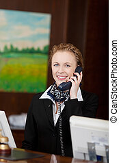 Young female receptionist answering the phone