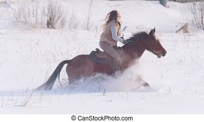 Young female rider riding a black horse through the drifts...