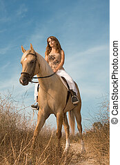 Young female riding on horse  in deserted rural location
